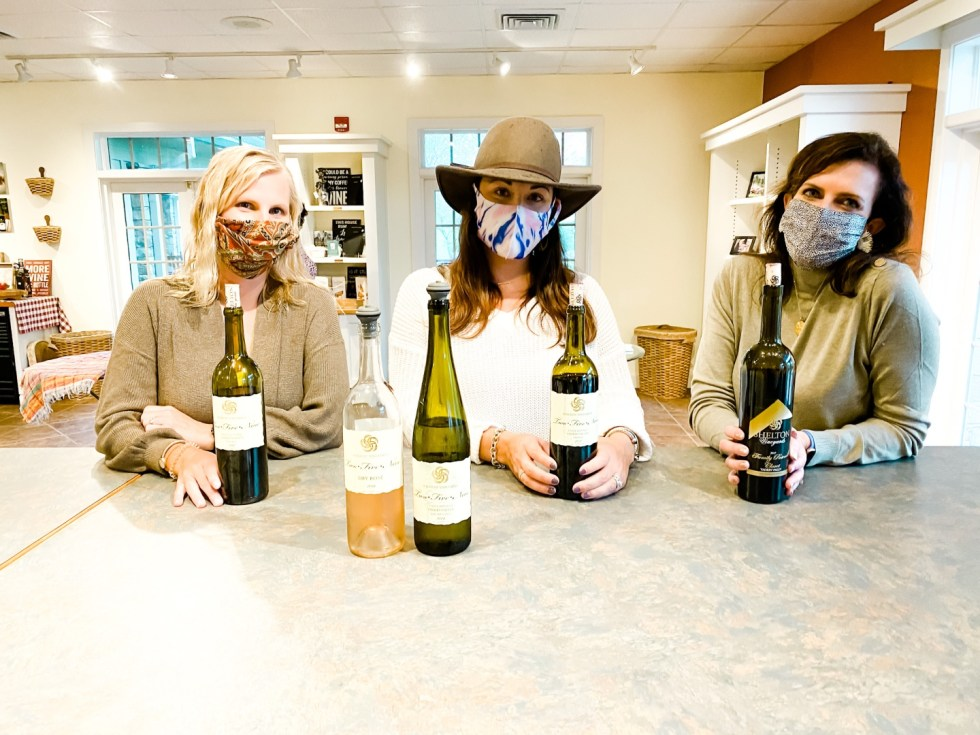 2020, a Year in Review: our Travel Adventures - I'm Fixin' To - @imfixintoblog |Year in Review by popular NC travel blog, I'm Fixin' To: image of three women wearing face masks and sitting at a cement counter top with bottles of red and white wine.