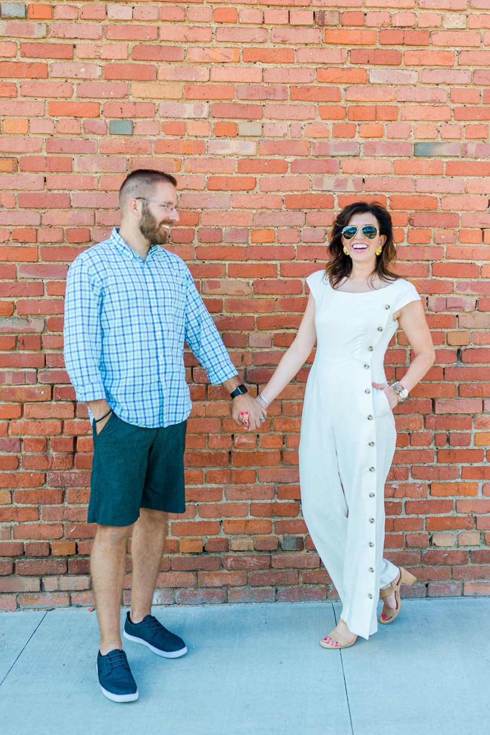 10 Year Anniversary by popular NC lifestyle blog, I'm Fixin' To: image of a husband and wife standing together and holding hands in front of a red brick building and wearing a white jumpsuit, blue plaid button up shirt, blue shorts, blue sneakers, and tan block heel sandals.