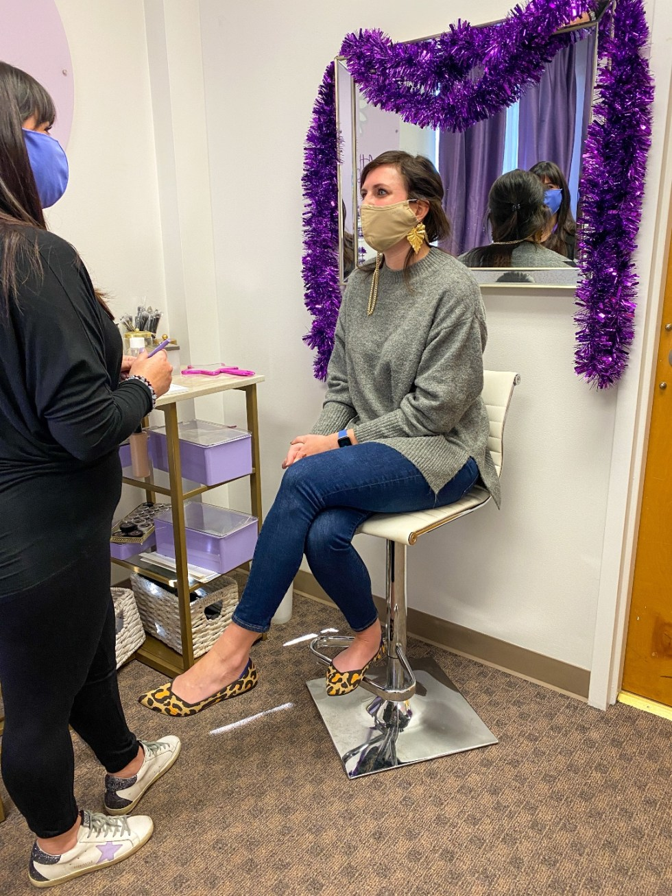A Custom Foundation Blend at Colette Skincare - I'm Fixin' To - @imfixintoblog |Custom Foundation Blend by popular NC beauty blog, I'm Fixin' To: image of a woman sitting in a white barstool chair in front of a mirror decorated with purple tinsel at Colette Skincare and talking to a makeup consultant wearing an all black outfit.
