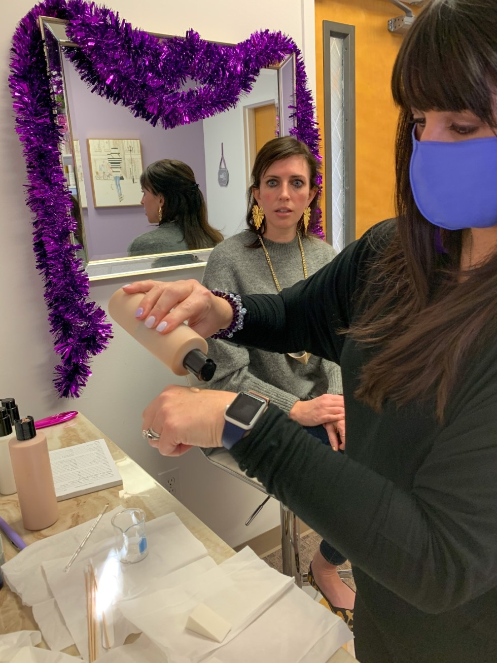 A Custom Foundation Blend at Colette Skincare - I'm Fixin' To - @imfixintoblog |Custom Foundation Blend by popular NC beauty blog, I'm Fixin' To: image of a woman sitting in a white barstool chair in front of a mirror decorated with purple tinsel at Colette Skincare and watching a woman put foundation on her hand.