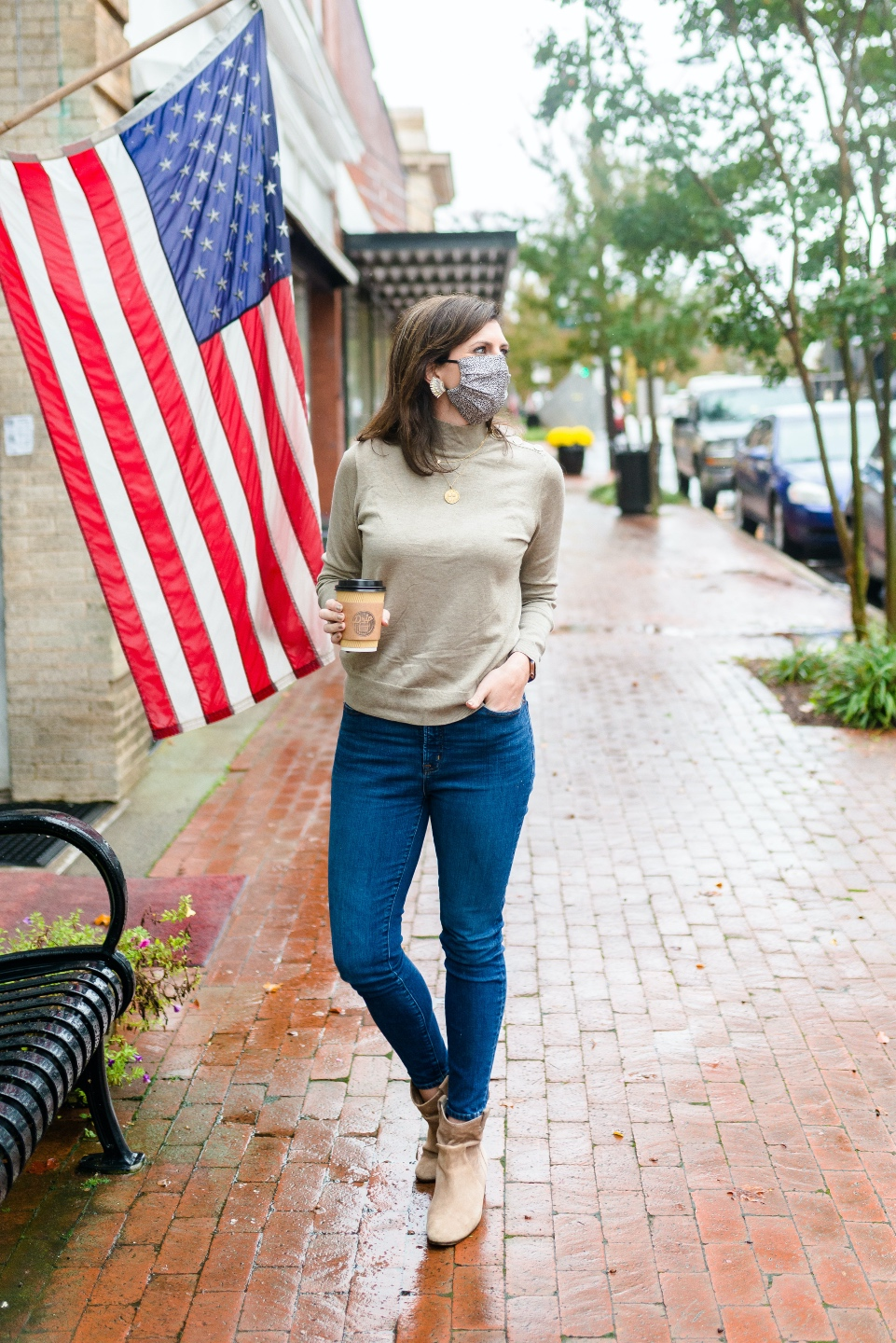 Counties in NC by popular NC blog, I'm Fixin' To: image of a woman walking on a brick pathway and wearing a tan sweater, leopard print face mask, jeans, and tan ankle boots.