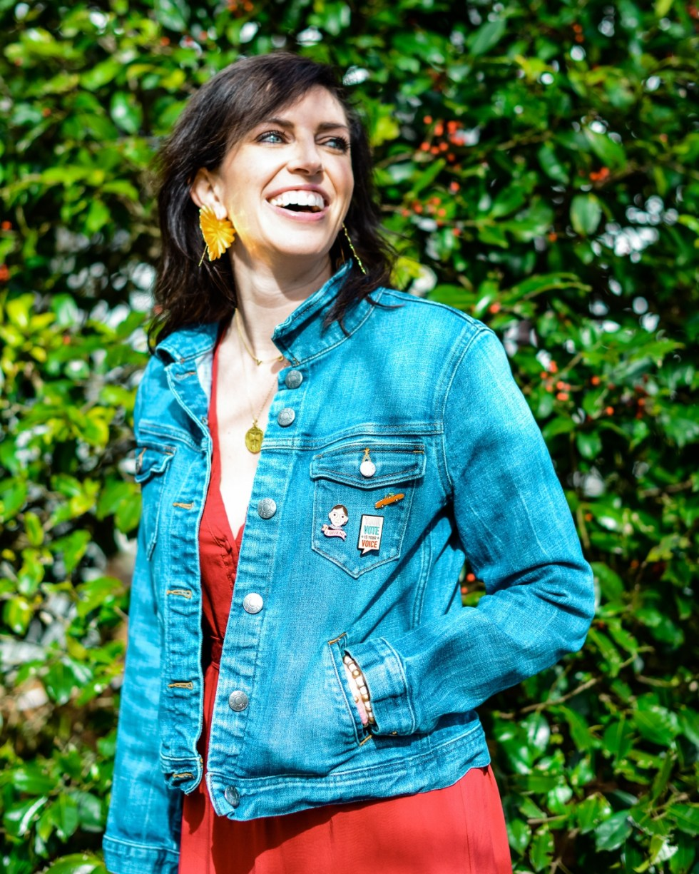 Statement Earrings by popular NC fashion blog, I'm Fixin' To: image of a woman wearing a denim jacket, red dress, gold coin necklace, and gold leaf statement earrings.