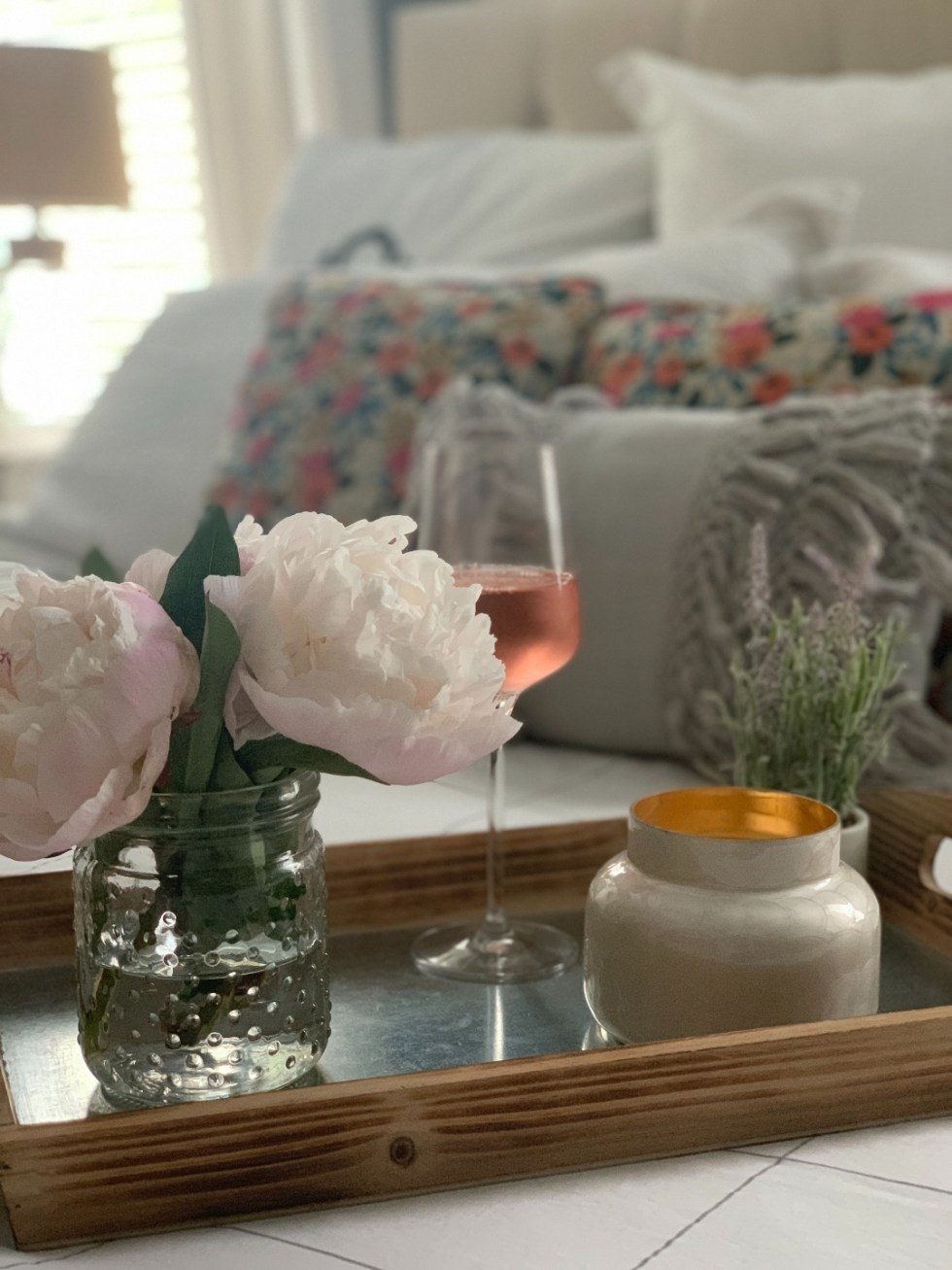 How to Make your Home Cozy: 10 Easy Ways - I'm Fixin' To - @imfixintoblog |How to Make Your Home Cozy by popular NC life and style blog, I'm Fixin' To: image of a serving tray set with a vase of flowers, candle, and glass of wine.