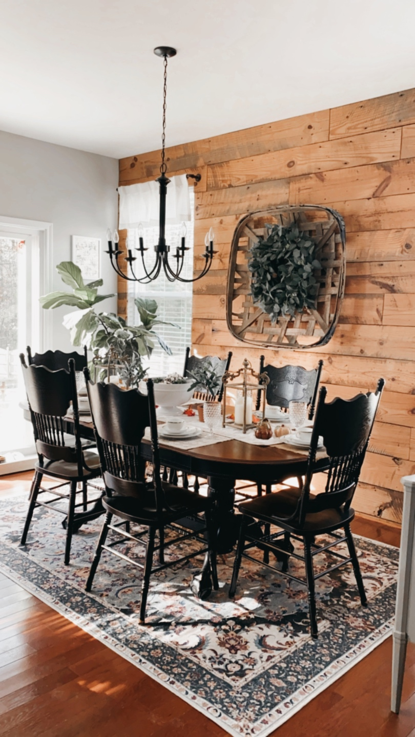 How to Make your Home Cozy: 10 Easy Ways - I'm Fixin' To - @imfixintoblog |How to Make Your Home Cozy by popular NC life and style blog, I'm Fixin' To: image of a black dining table with black chairs on a floral print area rug in front of a wood shiplap wall with a black chandelier hanging over it.