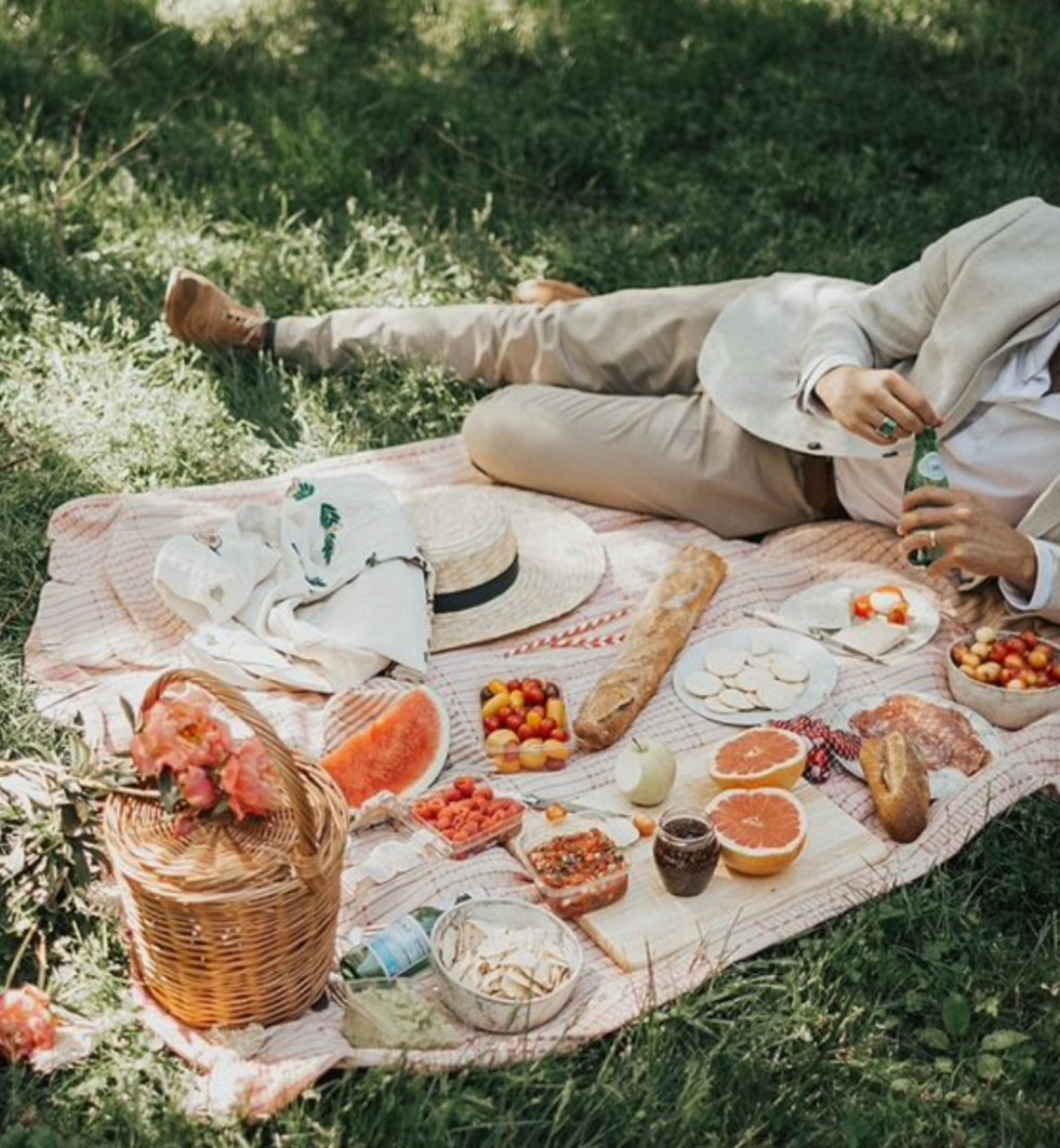 What Inspires Me by popular NC lifestyle blog, I'm Fixin' To: image of a man laying on a blanket on the grass that's covered with watermelon slices, grapefruit slices, cherry tomatoes, bread, sliced meat, cheese, and crackers.