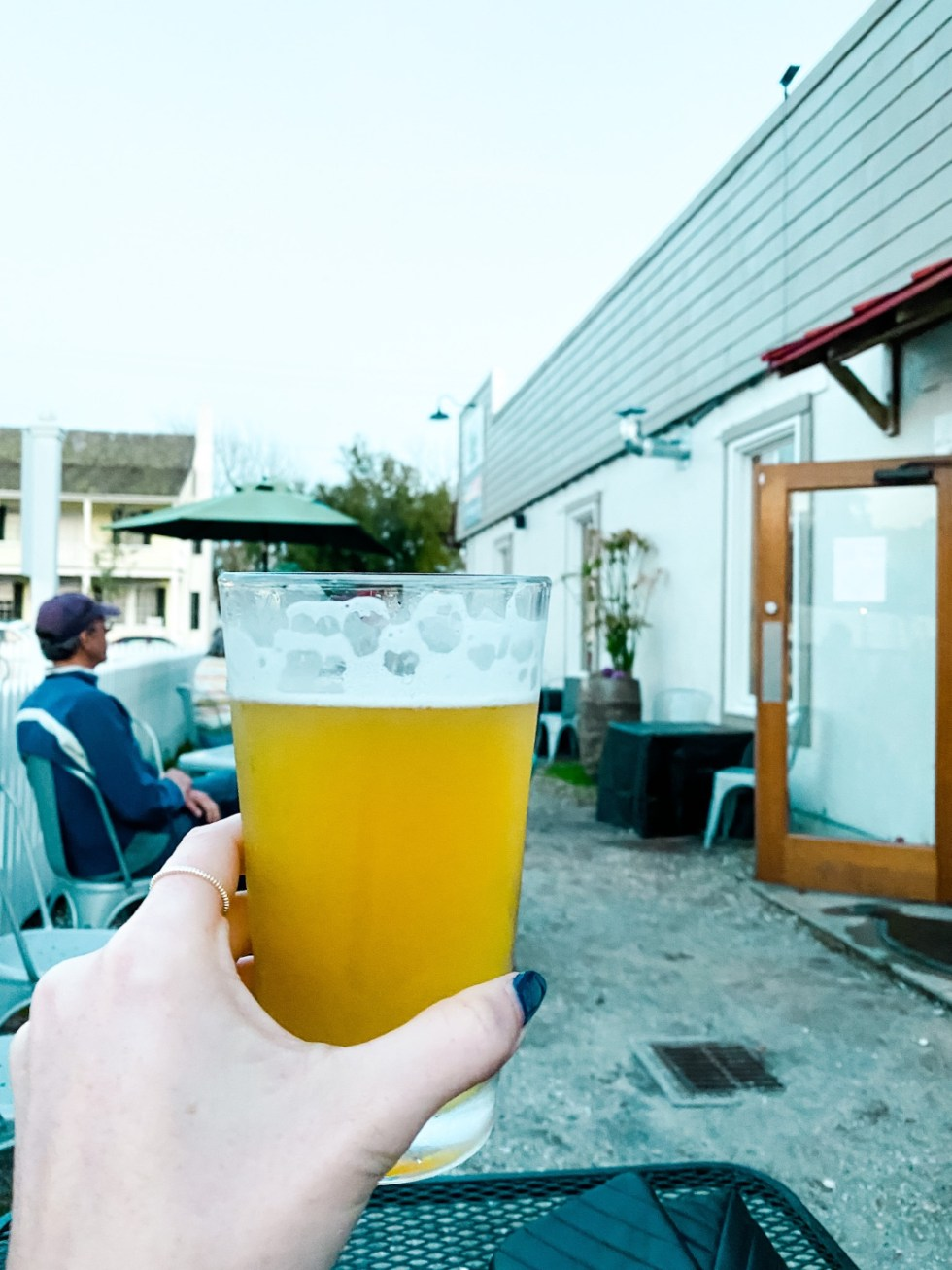 Weekend Travel: The Best Things to Do in Beaufort NC in 48 Hours - I'm Fixin' To - @imfixintoblog |Things to Do in Beaufort NC by popular NC travel blog, I'm Fixin' To: image of a woman holding a glass of beer in her hand.