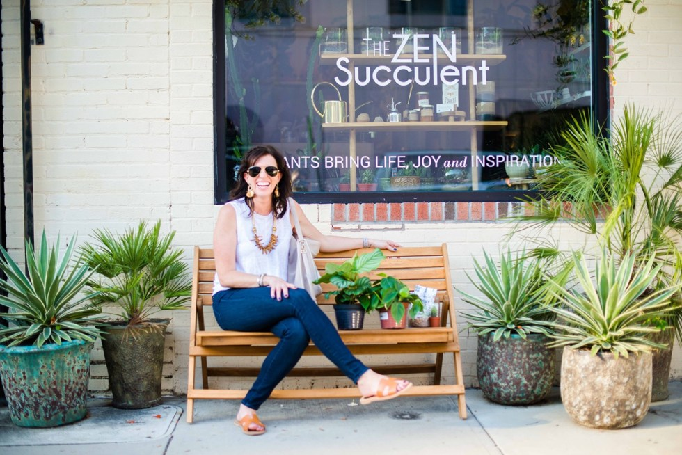 Women Owned Businesses by popular NC lifestyle blog, I'm Fixin' To: image of a woman sitting on a wooden bench outside in front of the Zen Succulent.