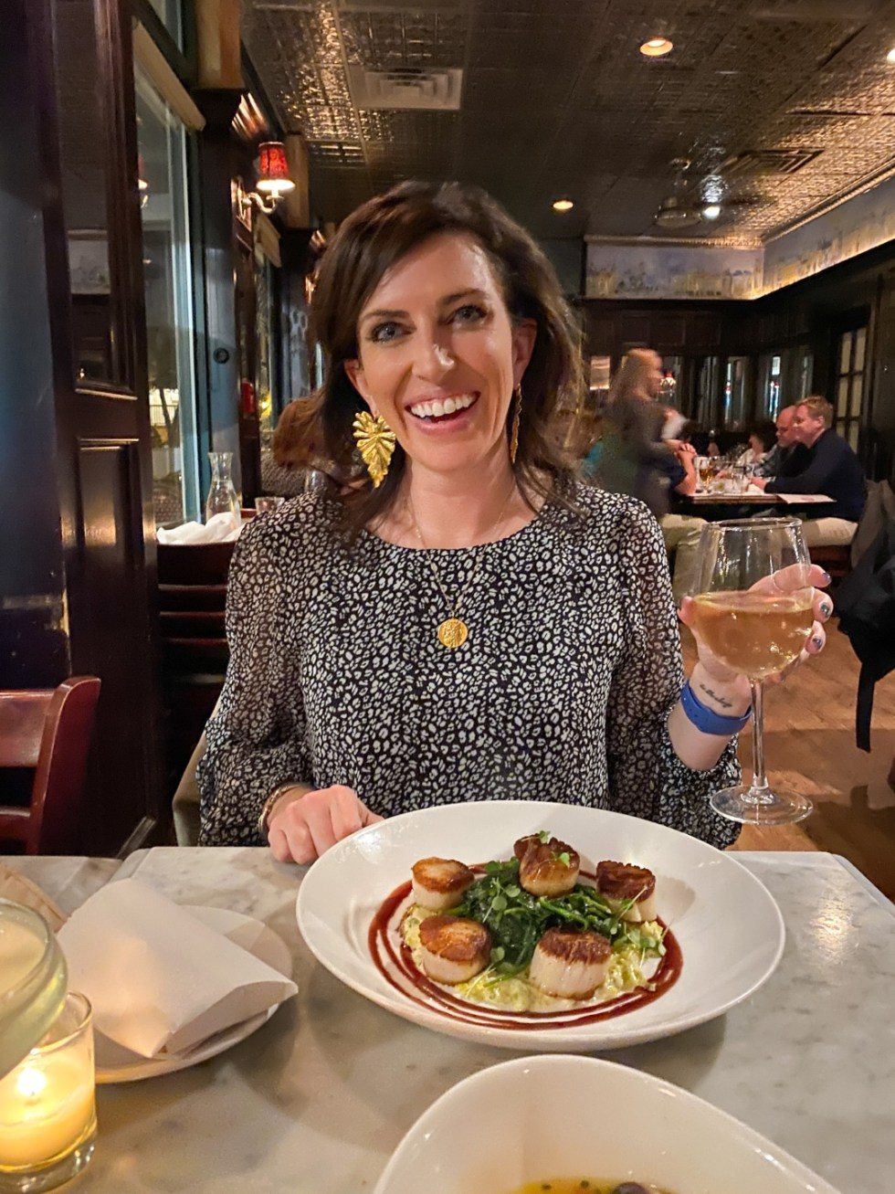 A Spring Weekend in Wilmington, NC: the Best Things to Do - I'm Fixin' To - @imfixintoblog |Weekend in Wilmington by popular NC travel blog, I'm Fixin' To: image of a woman holding a glass of white wine and sitting in front of a plate of scallops.