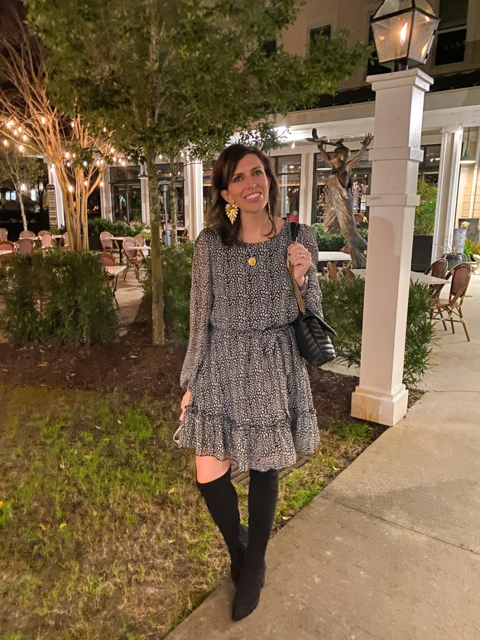 A Spring Weekend in Wilmington, NC: the Best Things to Do - I'm Fixin' To - @imfixintoblog |Weekend in Wilmington by popular NC travel blog, I'm Fixin' To: image of a woman wearing black over the knee boots and a black and white leopard print long sleeve chiffon dress with gold statement earrings and a gold pendant necklace.