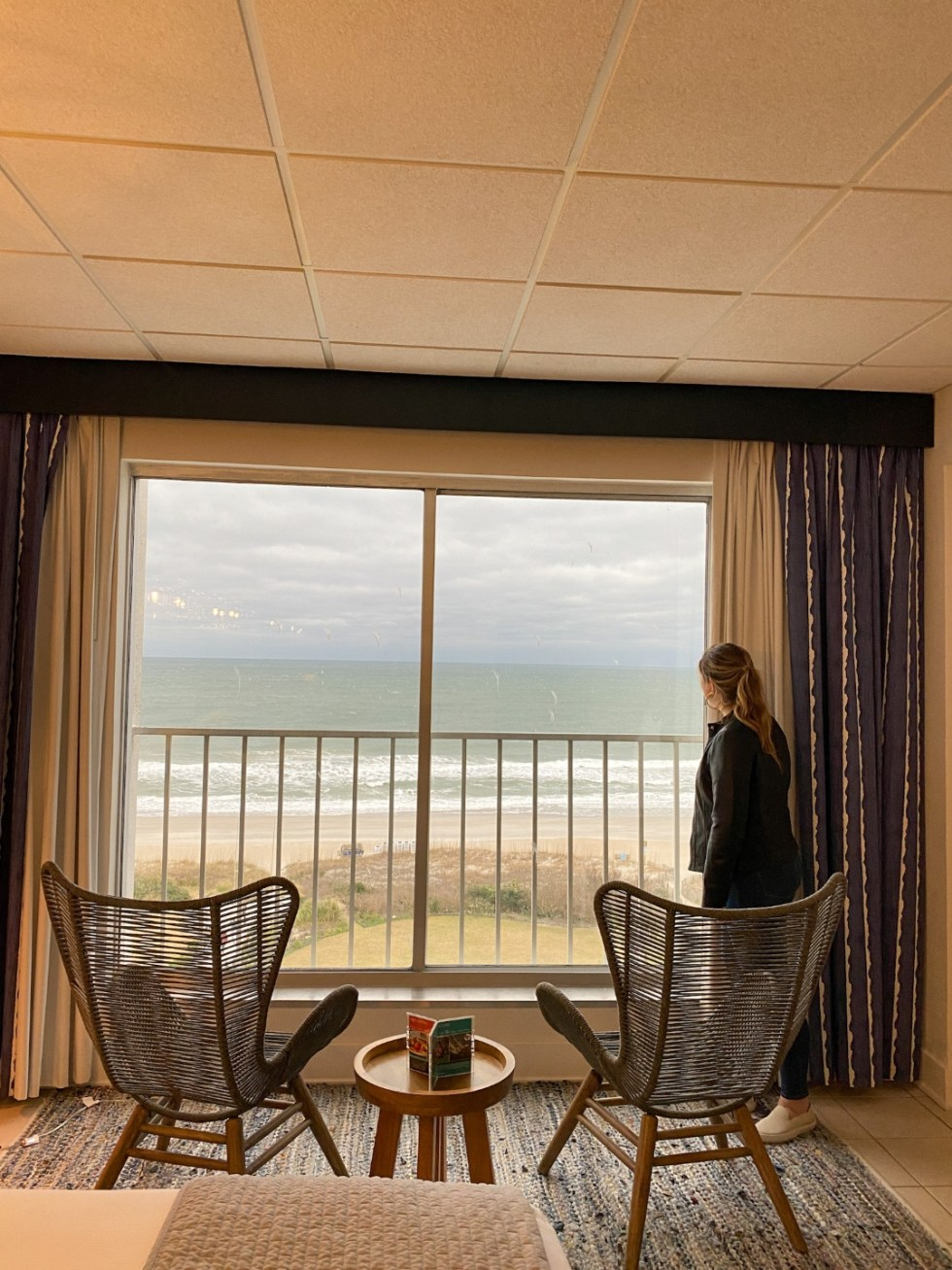 A Spring Weekend in Wilmington, NC: the Best Things to Do - I'm Fixin' To - @imfixintoblog |Weekend in Wilmington by popular NC travel blog, I'm Fixin' To: image of a woman standing in a hotel room and looking at the beach out a large picture window.