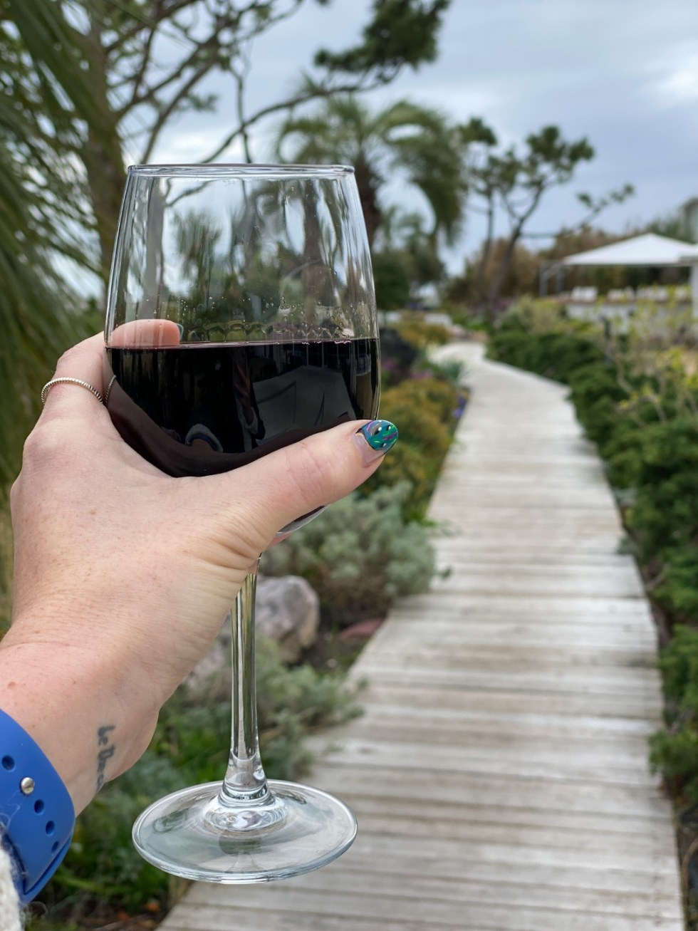 A Spring Weekend in Wilmington, NC: the Best Things to Do - I'm Fixin' To - @imfixintoblog |Weekend in Wilmington by popular NC travel blog, I'm Fixin' To: image of a woman holding a glass of red wine on a wooden boardwalk.