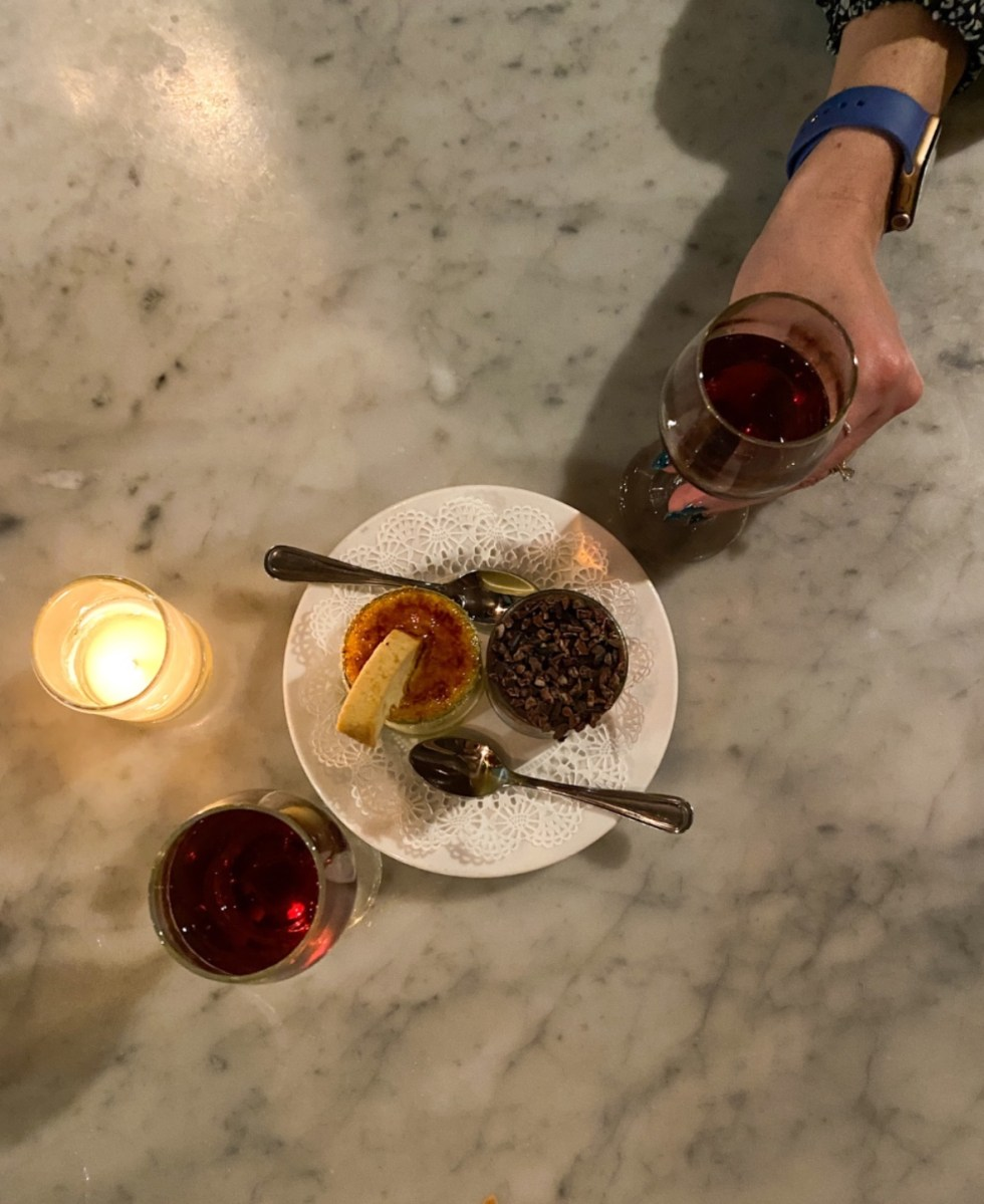 A Spring Weekend in Wilmington, NC: the Best Things to Do - I'm Fixin' To - @imfixintoblog |Weekend in Wilmington by popular NC travel blog, I'm Fixin' To: image of creme brulee and two glasses of red wine.