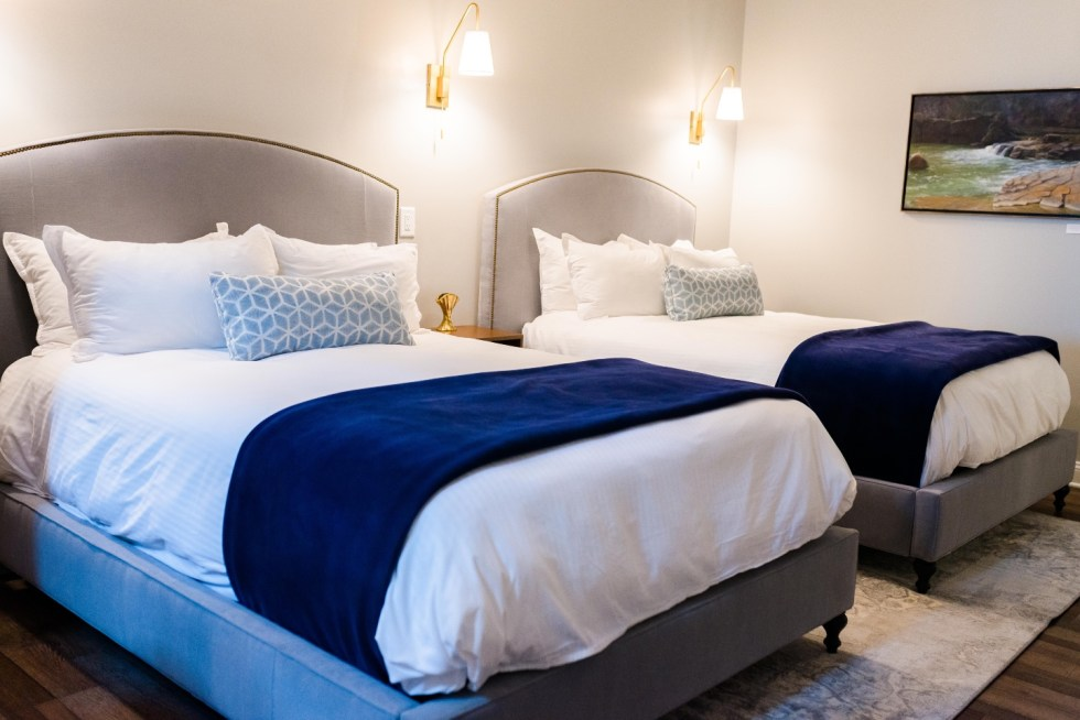 Places to Stay: The Colonial Inn in Hillsborough NC - I'm Fixin' To - @imfixintoblog |The Colonial Inn Hillsborough NC by popular NC travel blog, I'm Fixin' To: image of two twin size beds with grey fabric covered head boards, white bedding, blue and white lumbar pillows and blue throw blankets.
