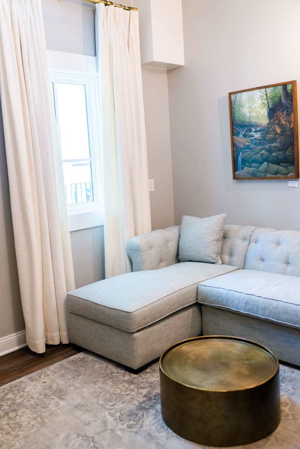 Places to Stay: The Colonial Inn in Hillsborough NC - I'm Fixin' To - @imfixintoblog |The Colonial Inn Hillsborough NC by popular NC travel blog, I'm Fixin' To: image of a grey sectional couch and round gold coffee table next to a window with white drapes.