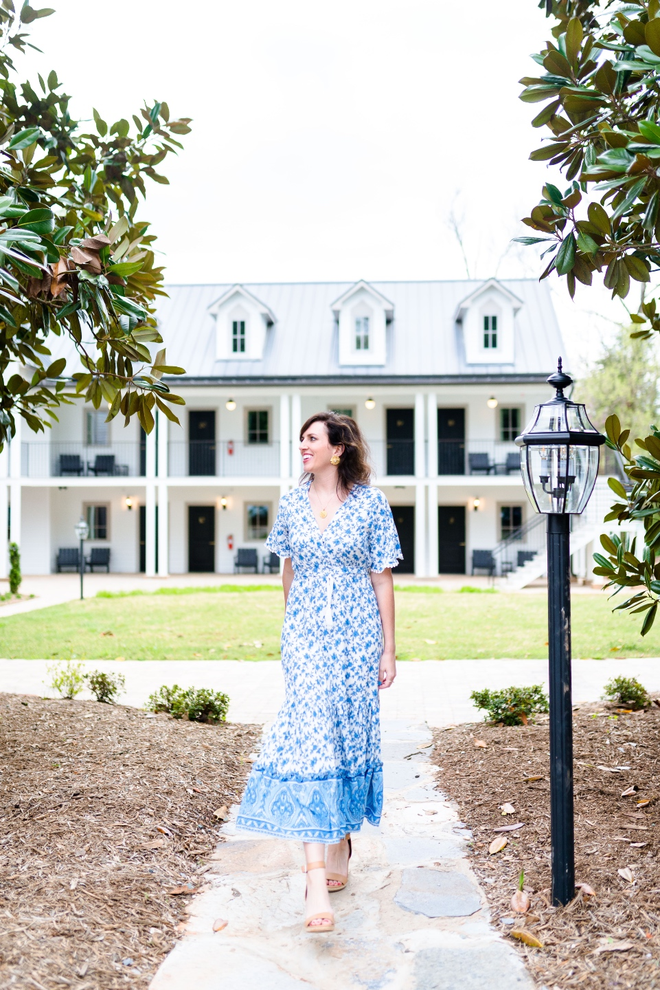 Places to Stay: The Colonial Inn in Hillsborough NC |The Colonial Inn Hillsborough NC by popular NC travel blog, I'm Fixin' To: image of a woman wearing a blue floral print maxi dress and standing outside of the Colonia Inn.
