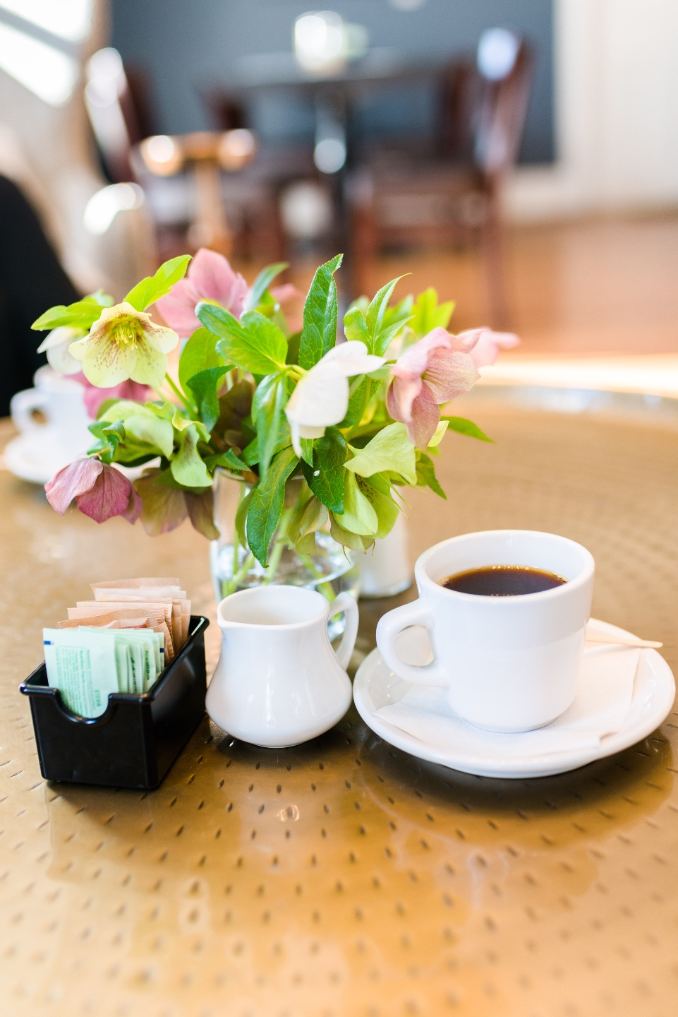 Places to Stay: The Colonial Inn in Hillsborough NC - I'm Fixin' To - @imfixintoblog |The Colonial Inn Hillsborough NC by popular NC travel blog, I'm Fixin' To: image of flowers in a vase next to a cup of coffee and sugar packets.