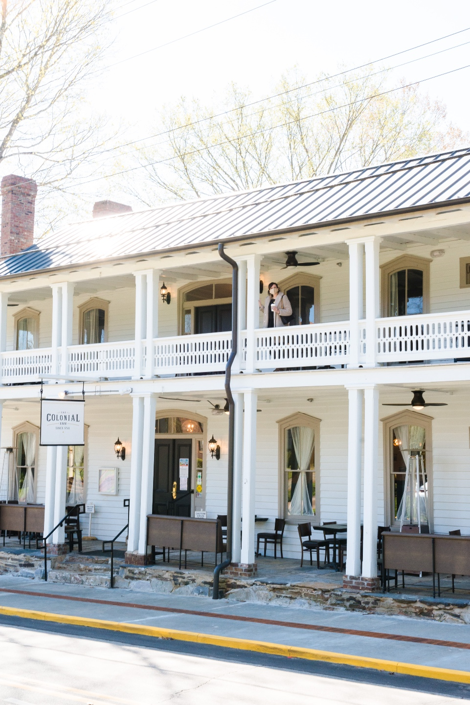 Places to Stay: The Colonial Inn in Hillsborough NC - I'm Fixin' To - @imfixintoblog |The Colonial Inn Hillsborough NC by popular NC travel blog, I'm Fixin' To: image of a woman standing outside at the The Colonia Inn in Hillsborough NC.