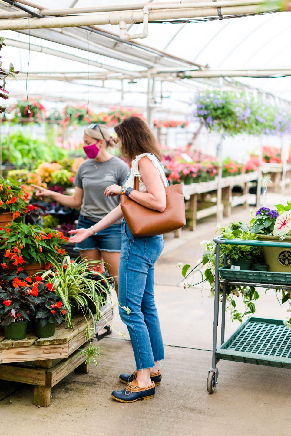 5 Spring Planting Tips with Fairview Garden Center - I'm Fixin' To - @imfixintoblog |Best Plants to Plant in Spring by popular NC lifestyle blog: image of two women looking at red floral plants a the Fairview Garden Center.