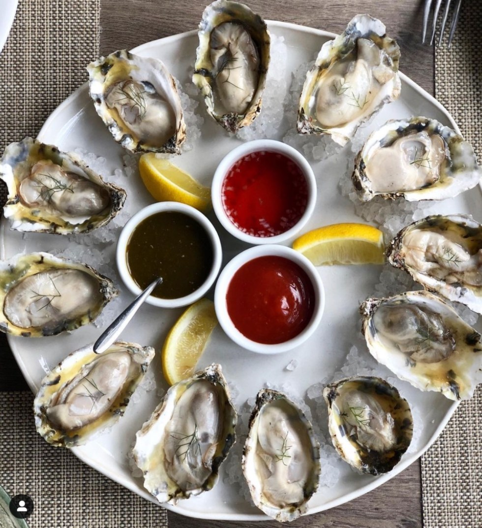 Raleigh Oyster Crawl: a Complete Guide to the Best Local Oyster Bars - I'm Fixin' To - @imfixintoblog | Raleigh Oyster Crawl by popular North Carolina blog, I'm Fixin' To: image of oysters on a white plate with lemon wedges and three ceramic bowls filled with different dipping sauces.