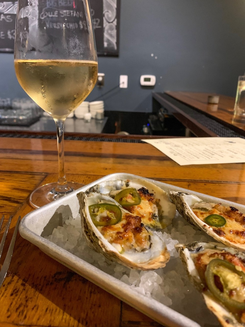 10 Iconic Dishes to Try in Raleigh - I'm Fixin' To - @imfixintoblog } Best Food in Raleigh NC by popular NC lifestyle blog, I'm Fixin' To: image of oysters and a glass of white wine.