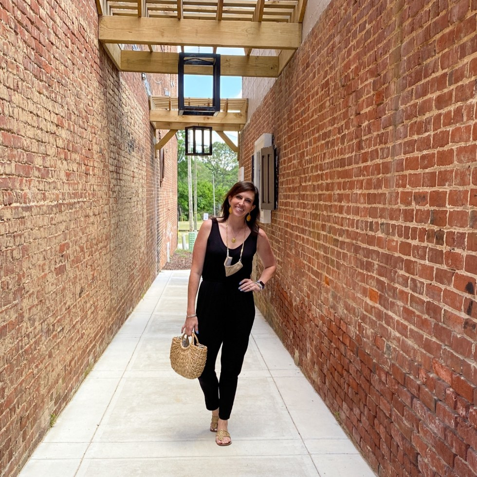 Style Diary: What I've Been Wearing this Spring - I'm Fixin' To - @imfixintoblog | Spring Essentials by popular NC fashion blog, I'm Fixin' To: image of a woman wearing a black jumpsuit, bold accent necklace, gold sandals and holding a woven sea grass handbag.