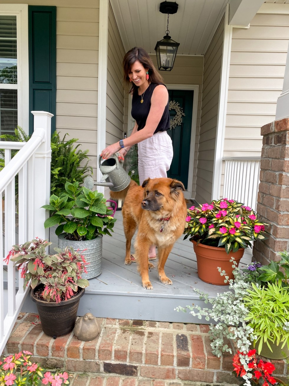 Style Diary: What I've Been Wearing this Spring - I'm Fixin' To - @imfixintoblog | Spring Essentials by popular NC fashion blog, I'm Fixin' To: image of a woman standing on her front porch and watering her plants while wearing black tank top and white linen pants.
