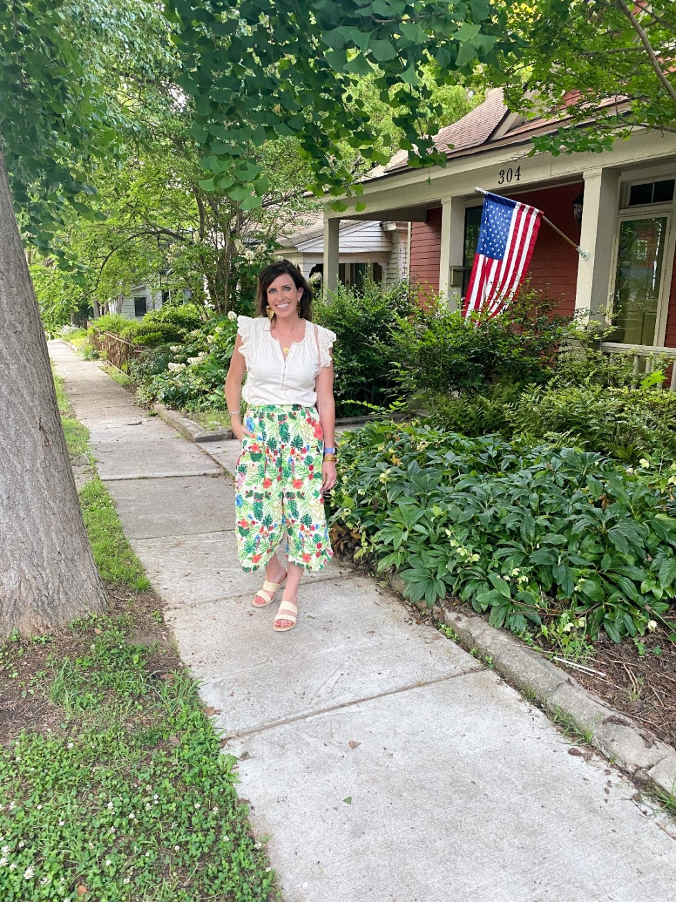 Style Diary: What I've Been Wearing this Spring - I'm Fixin' To - @imfixintoblog | Spring Essentials by popular NC fashion blog, I'm Fixin' To: image of a woman walking down a sidewalk and wearing a white eyelet flutter sleeve top with tropical print pants and slide sandals.