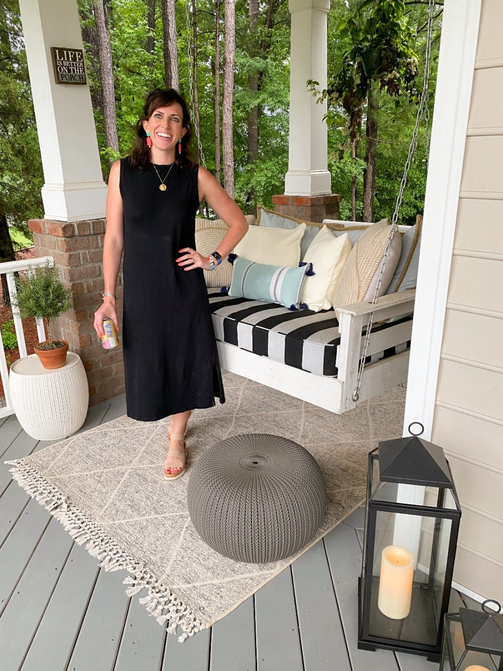 Style Diary: What I've Been Wearing this Spring - I'm Fixin' To - @imfixintoblog | Spring Essentials by popular NC fashion blog, I'm Fixin' To: image of a woman standing on a porch next to a wooden porch swing with a black and white stripe cushion and wearing a black sleeveless maxi dress and colorful statement earrings.
