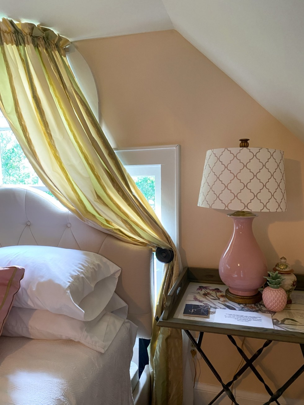 Top 10 Best Things to Do in Edenton, NC: A Complete Travel Guide - I'm Fixin' To - @imfixintoblog | Edenton Travel Guide by popular NC travel guid, I'm Fixin' To: image of a room with two pink base lamps, round end tables, bed with a white tuft upholstered headboard white bedding.