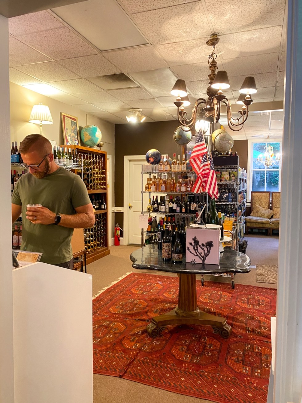 Top 10 Best Things to Do in Edenton, NC: A Complete Travel Guide - I'm Fixin' To - @imfixintoblog | Edenton Travel Guide by popular NC travel guid, I'm Fixin' To: image of a man looking at some bottles of wine.