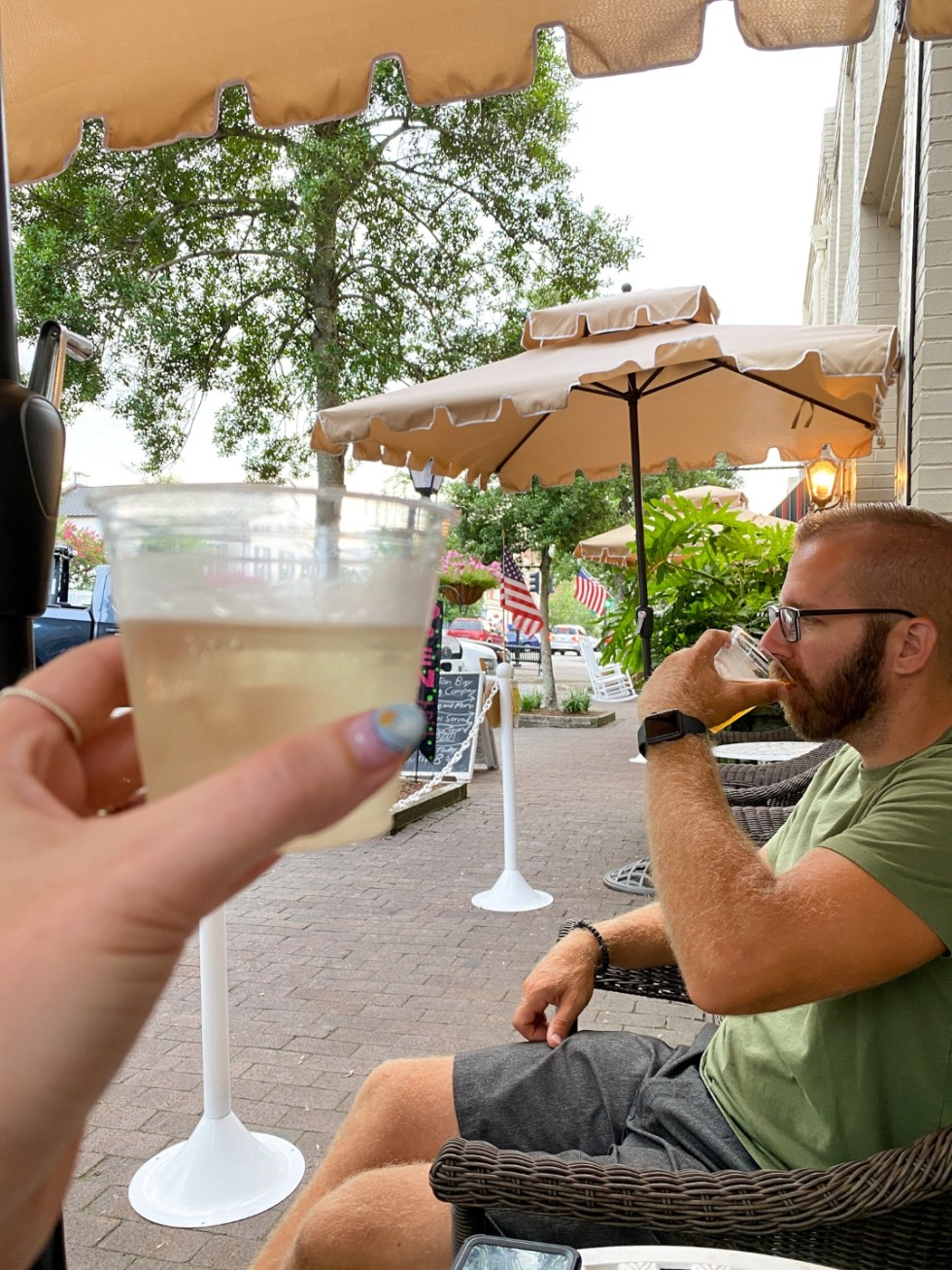 Top 10 Best Things to Do in Edenton, NC: A Complete Travel Guide - I'm Fixin' To - @imfixintoblog | Edenton Travel Guide by popular NC travel guid, I'm Fixin' To: image of a man and woman sitting under a tan fabric umbrella and drinking white wine in plastic cups.