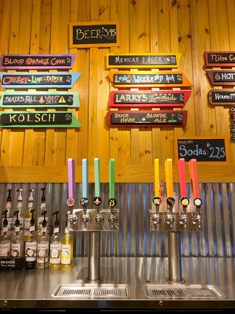 Top 10 Best Things to Do in Edenton, NC: A Complete Travel Guide - I'm Fixin' To - @imfixintoblog | Edenton Travel Guide by popular NC travel guid, I'm Fixin' To: image of a wooden plant wall with a display of various beer names on colorful wooden boards nailed to it.