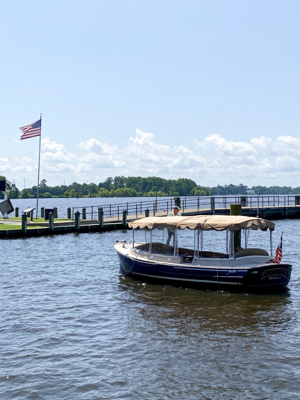 Top 10 Best Things to Do in Edenton, NC: A Complete Travel Guide - I'm Fixin' To - @imfixintoblog | Edenton Travel Guide by popular NC travel guid, I'm Fixin' To: image of a river boat on a river next to a dock.