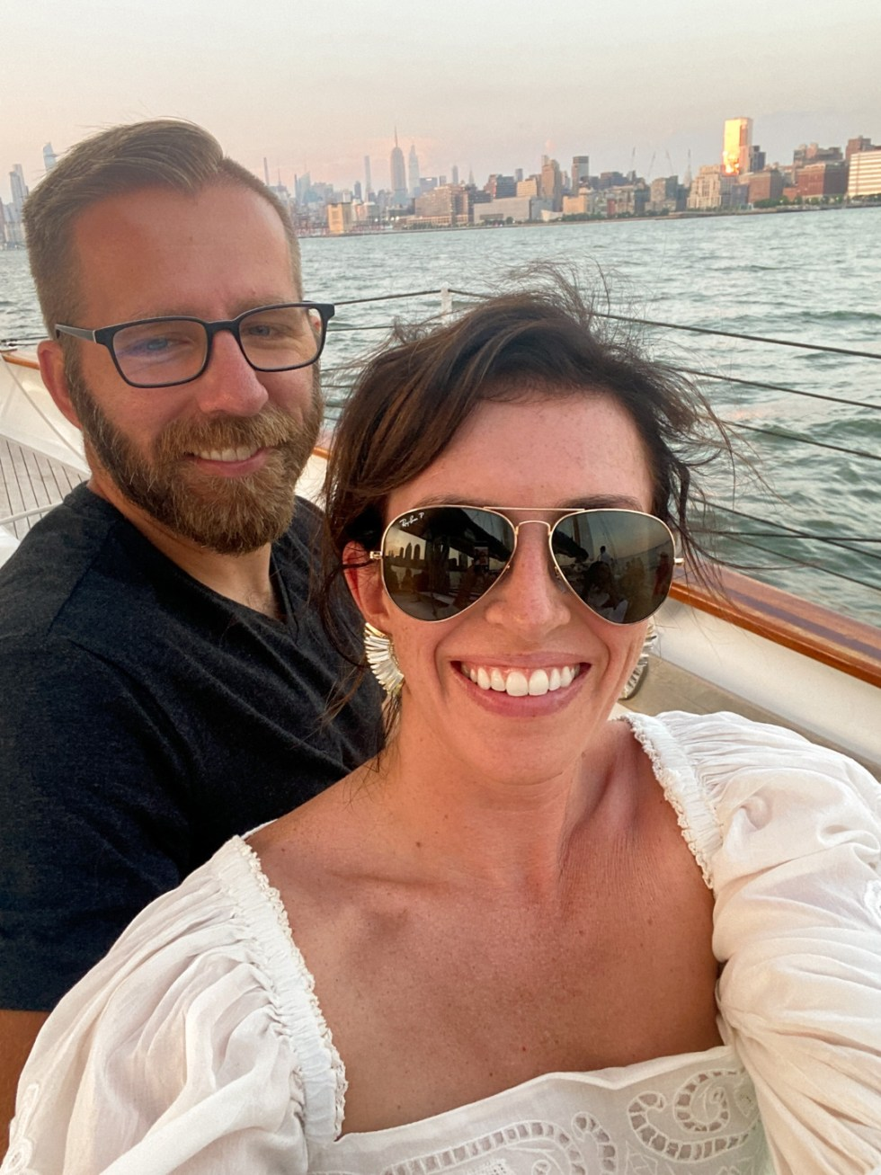 NYC Summer Weekend: Things to Do in NYC in the Summer - I'm Fixin' To - @imfixintoblog   NYC Summer Weekend by popular NC travel blog, I'm Fixin' To: image of a man and woman taking a selfie together on a boat with the NYC skyline behind them.