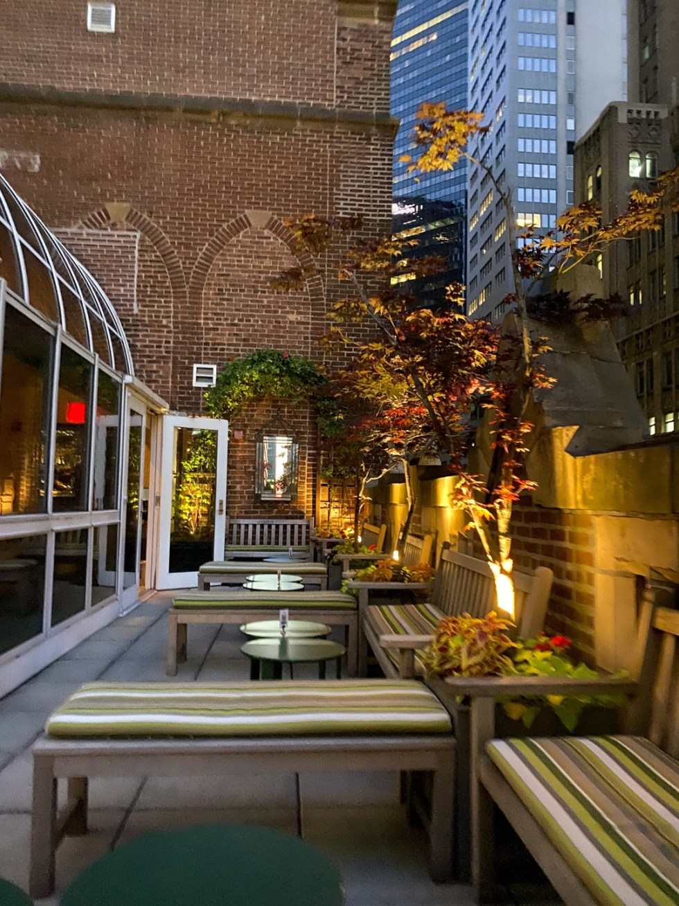 NYC Summer Weekend: Things to Do in NYC in the Summer - I'm Fixin' To - @imfixintoblog   NYC Summer Weekend by popular NC travel blog, I'm Fixin' To: image of a patio with black round coffee tables and wooden benches with tan and green stripe cushions.