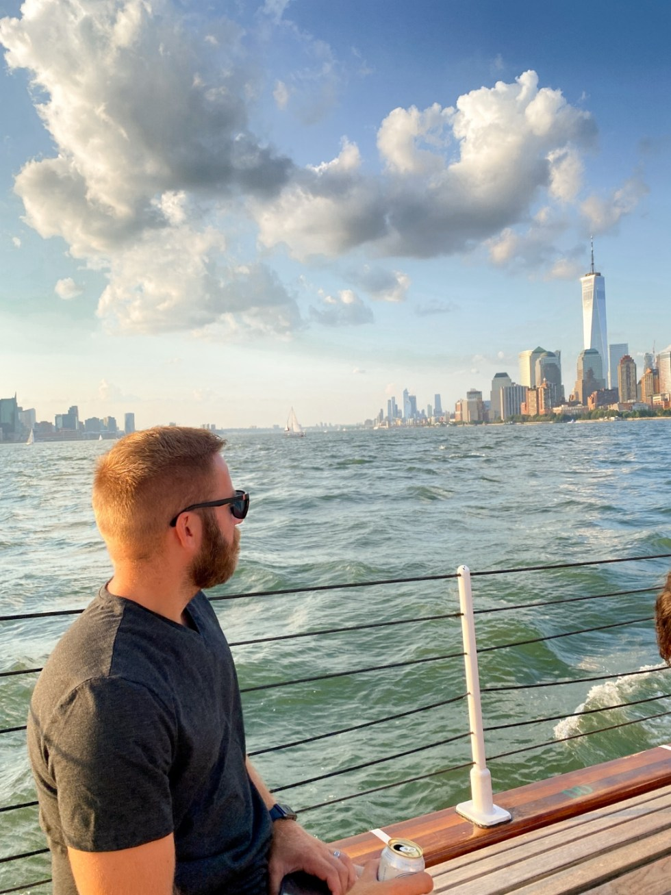 NYC Summer Weekend: Things to Do in NYC in the Summer - I'm Fixin' To - @imfixintoblog   NYC Summer Weekend by popular NC travel blog, I'm Fixin' To: image of a man sitting on a boat and looking out at the NYC skyline.