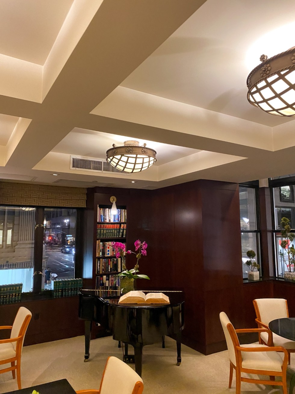 NYC Summer Weekend: Things to Do in NYC in the Summer - I'm Fixin' To - @imfixintoblog   NYC Summer Weekend by popular NC travel blog, I'm Fixin' To: image of a lounge with a black baby grand piano, bookcases, and round tables with tan upholstered chairs.