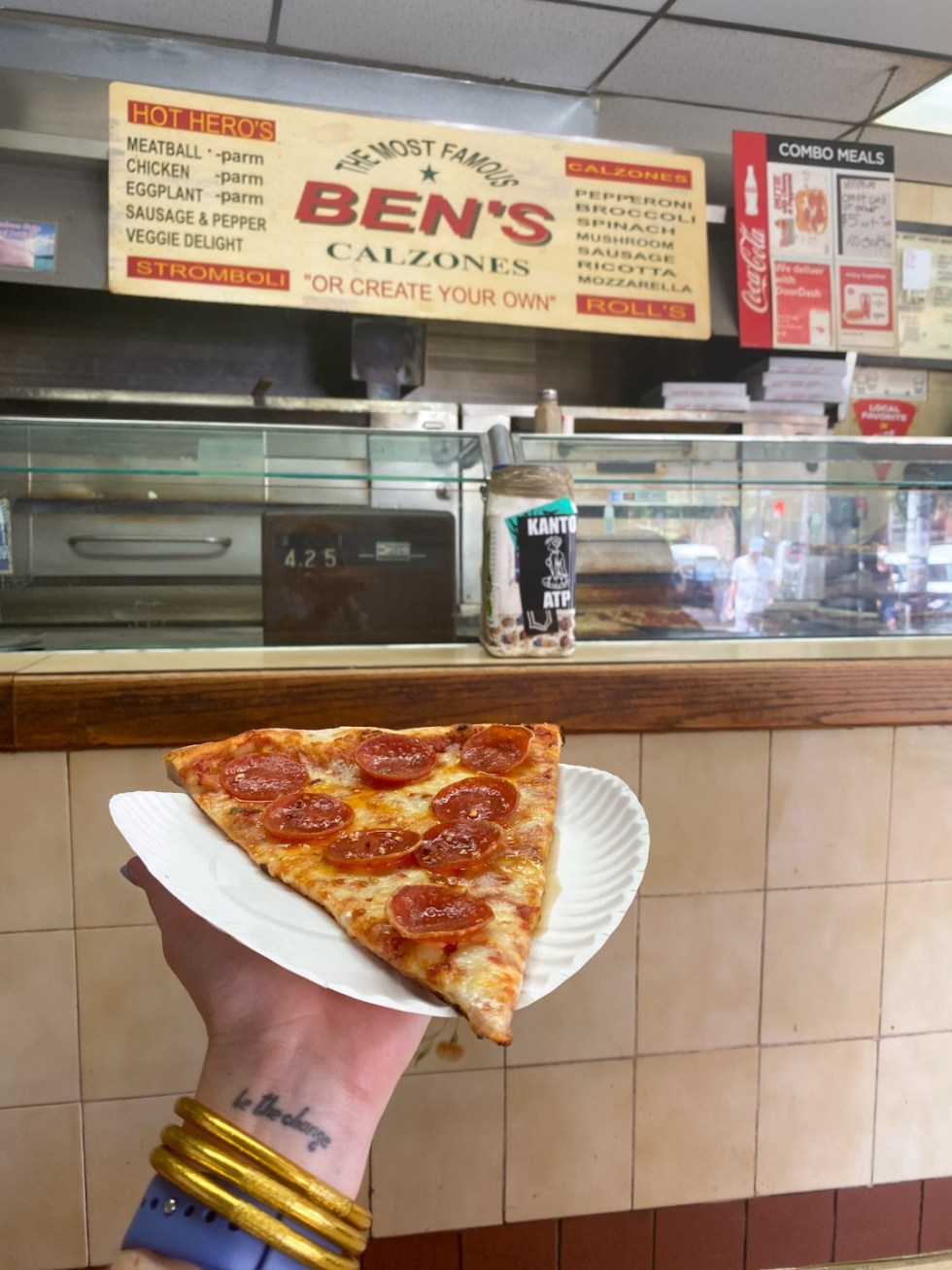 NYC Summer Weekend: Things to Do in NYC in the Summer - I'm Fixin' To - @imfixintoblog   NYC Summer Weekend by popular NC travel blog, I'm Fixin' To: image of a woman holding a slice of pepperoni pizza at Ben's Calzones.