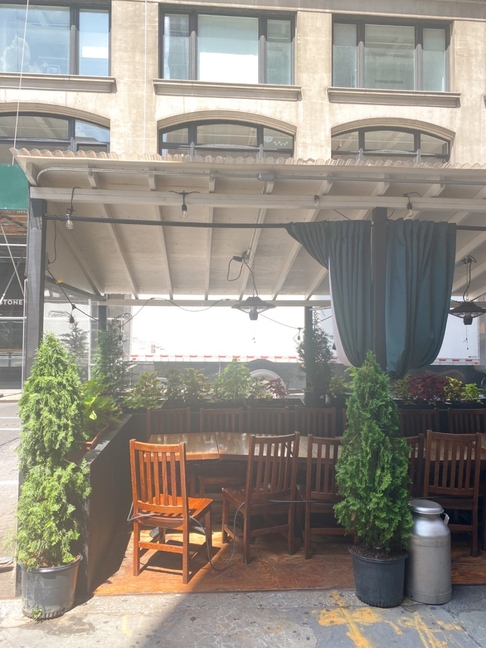 NYC Summer Weekend: Things to Do in NYC in the Summer - I'm Fixin' To - @imfixintoblog   NYC Summer Weekend by popular NC travel blog, I'm Fixin' To: image of a row of tables, wooden chairs, and potted plants.