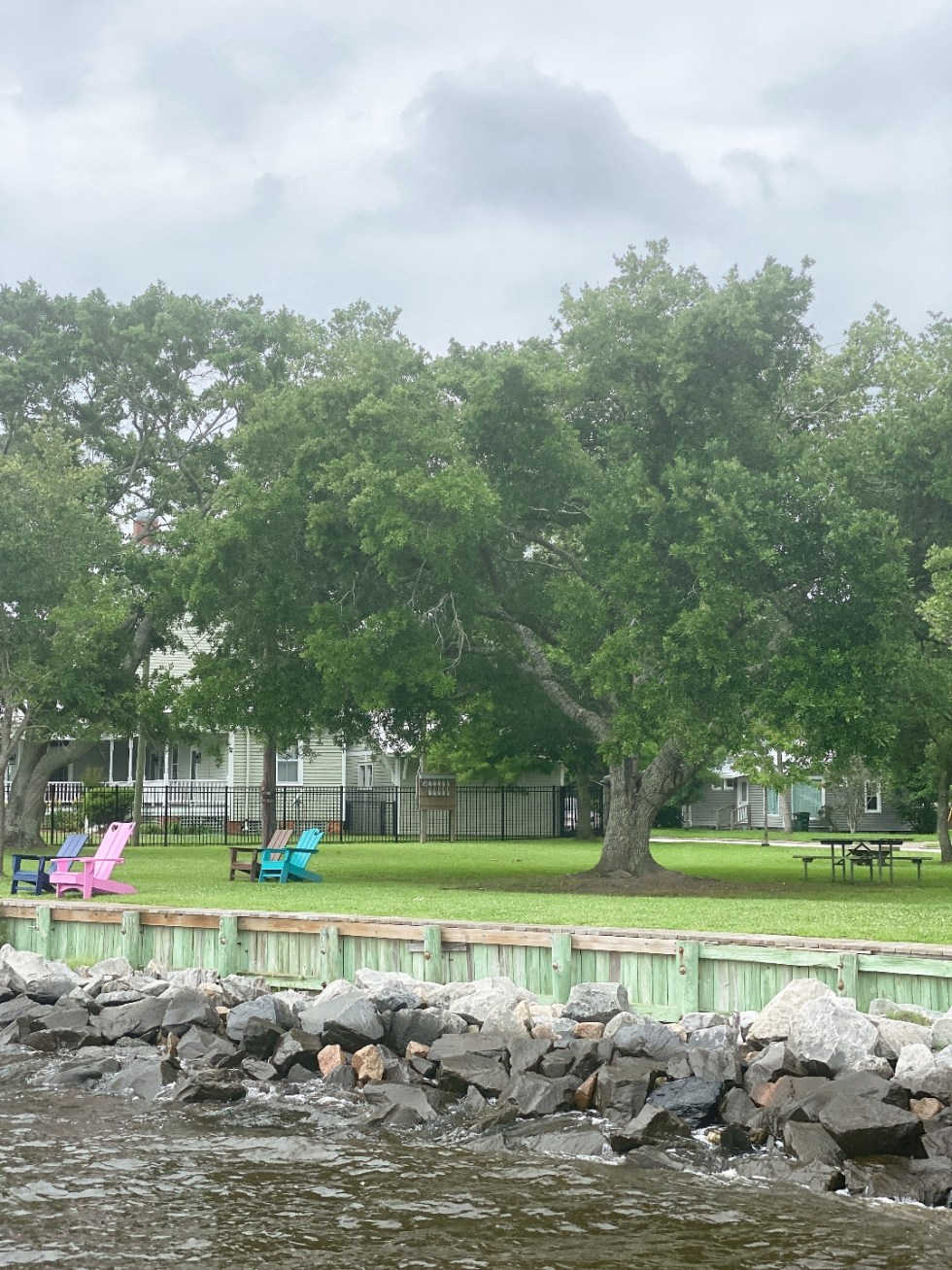 What to Do in Oriental, NC - I'm Fixin' To - @imfixintoblog | Things to do in Oriental NC by popular NC travel blog, I'm Fixin' To: image of some lounge chairs resting under some tall trees next to the ocean.