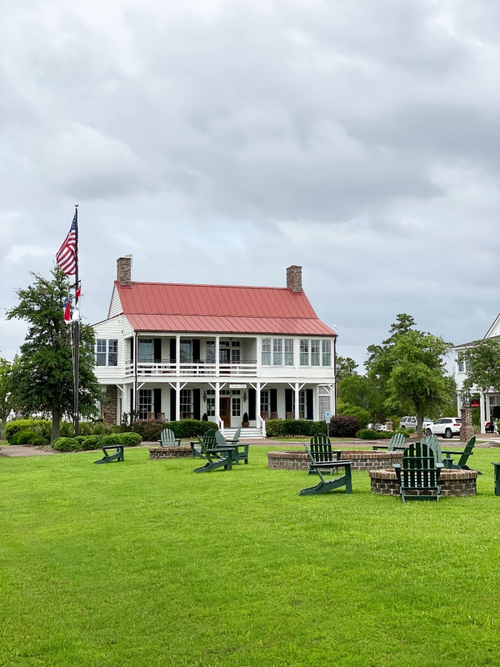 What to Do in Oriental, NC - I'm Fixin' To - @imfixintoblog | Things to do in Oriental NC by popular NC travel blog, I'm Fixin' To: image of a white building with a tall flag pole and wooden chairs and brick fire pits on the front lawn.