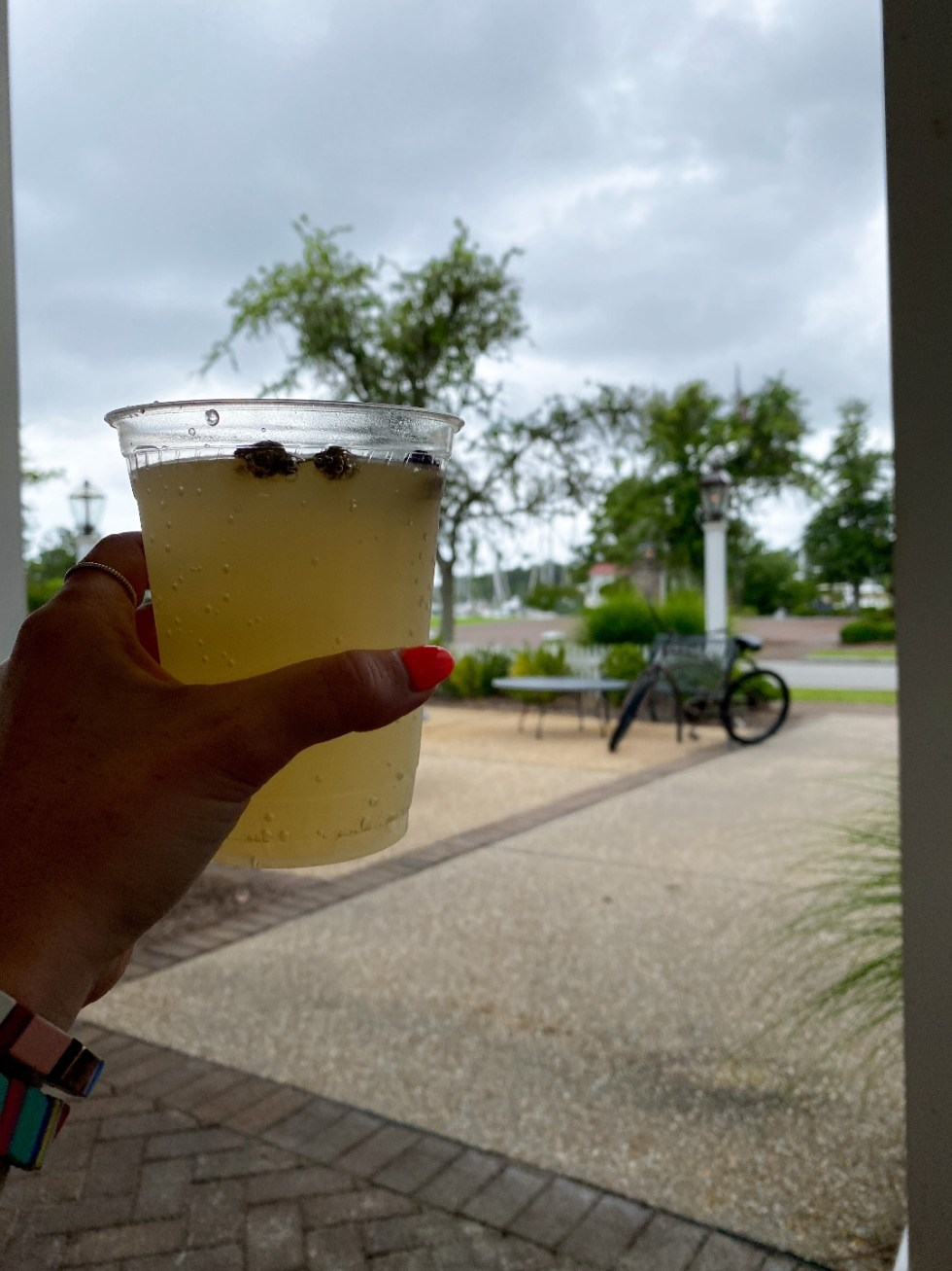 What to Do in Oriental, NC - I'm Fixin' To - @imfixintoblog | Things to do in Oriental NC by popular NC travel blog, I'm Fixin' To: image of a woman holding a cocktail in a clear plastic cup.