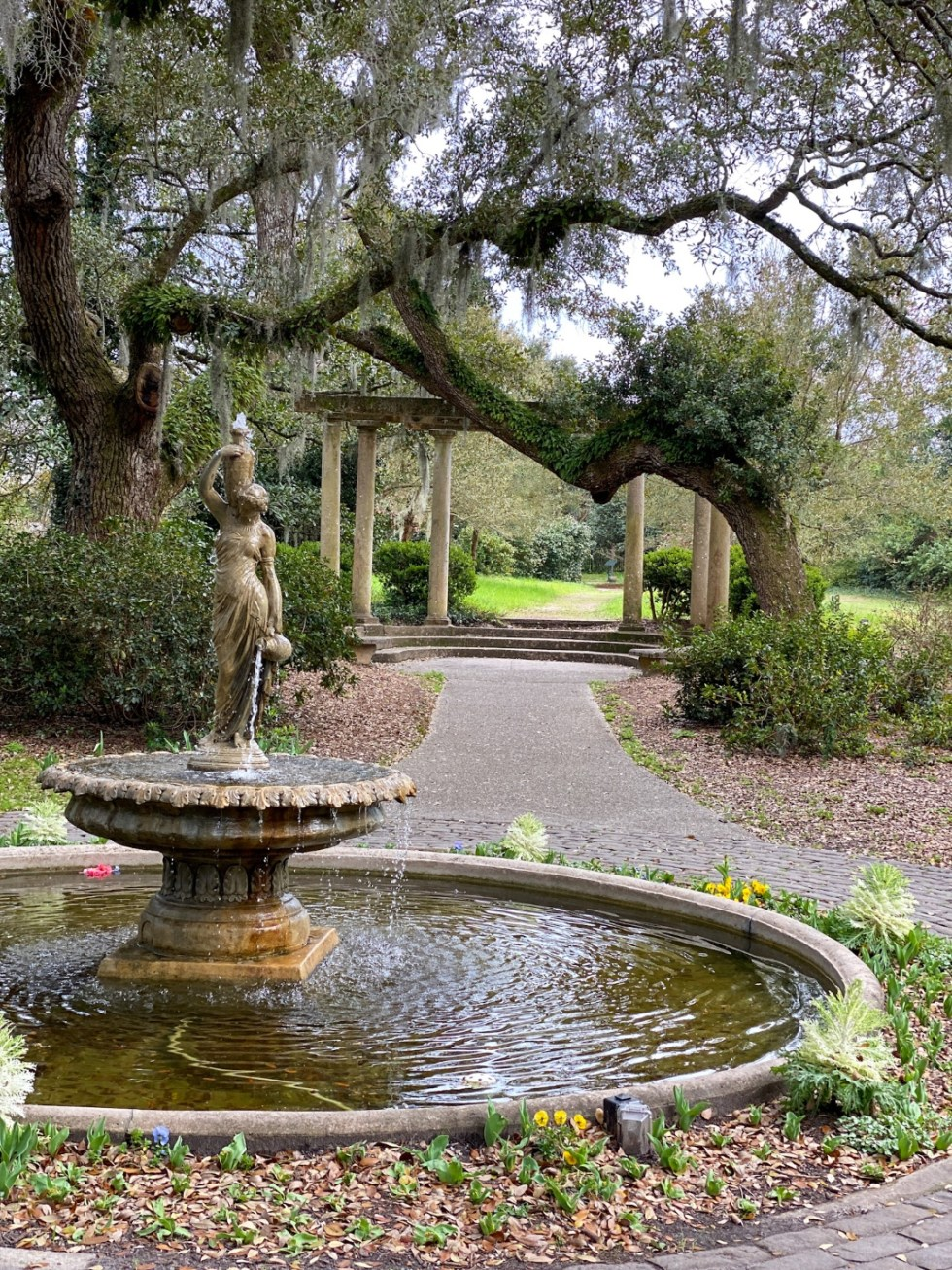 An Update on My North Carolina 100 County Tour - I'm Fixin' To - @imfixintoblog | Things to do in North Carolina by popular NC travel blog, I'm Fixin' To: image of a public garden with paved pathways, Grecian fountain and large oak tree covered in Spanish Moss.