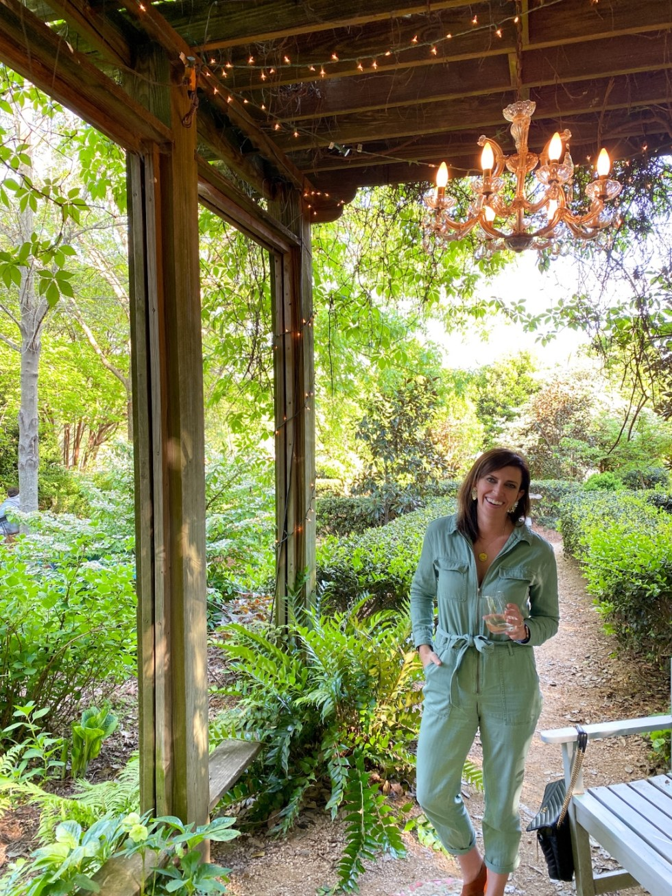 An Update on My North Carolina 100 County Tour - I'm Fixin' To - @imfixintoblog | Things to do in North Carolina by popular NC travel blog, I'm Fixin' To: image of a woman wearing a green jumpsuit and holding a glass of white wine.