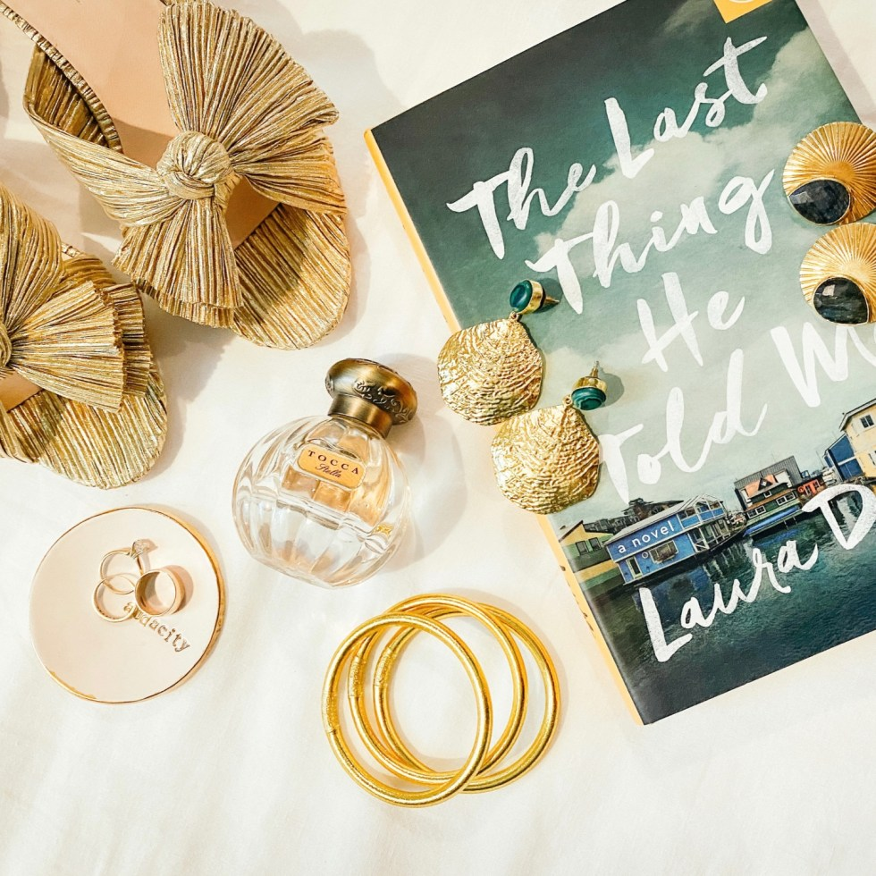 Recent Favorites: Top 10 Things I've Bought that Are Worth the Hype - I'm Fixin' To - @imfixintoblog | Recent Favorites by popular NC life and style blog, I'm Fixin' To: image of some gold accent earrings, gold rings, Tocca perfume, gold bow shoes, and the book The Last Thing He Told Me.