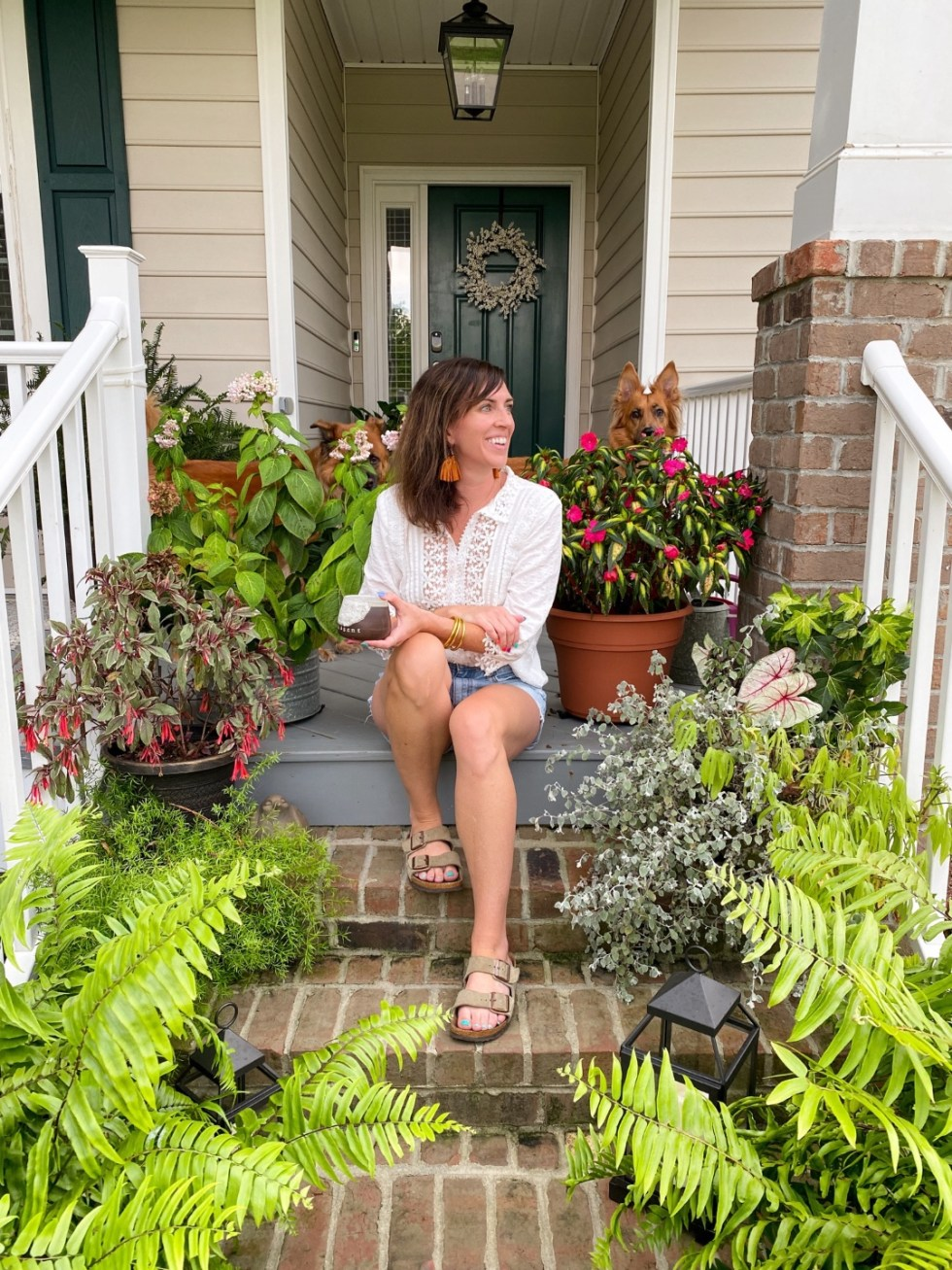 How to Wear White After Labor Day - I'm Fixin' To - @imfixintoblog   White After Labor Day by popular NC fashion blog, I'm Fixin' To: image of a woman sitting on her front porch steps and wearing a white blouse iwht brown strap sandals, and cut off denim shorts.