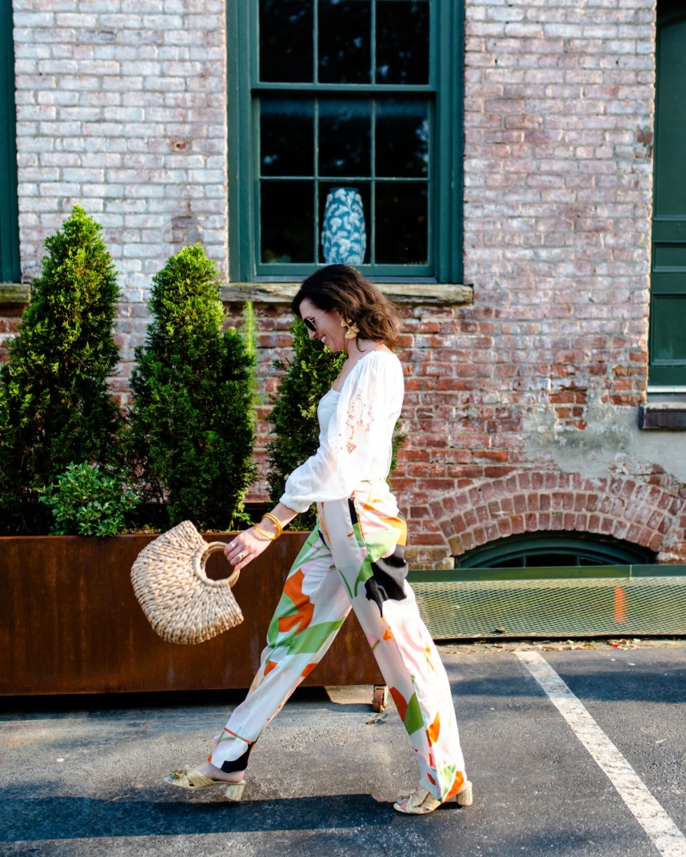 White After Labor Day by popular NC fashion blog, I'm Fixin' To: image of a woman wearing a white long lace sleeve top, abstract print pants, gold bow accent sandals, gold statement earrings, and holding a woven seagrass handbag.