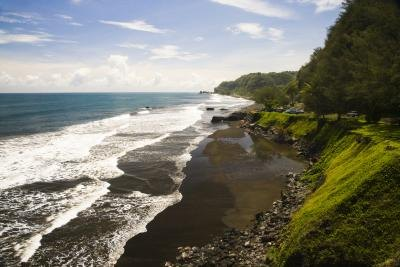 Tides roll into a beach with lush cliffs.