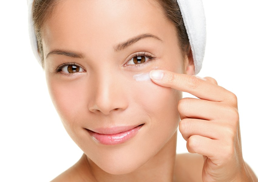 Face cream woman applying skin cream under eyes. Beauty eye contour cream wrinkle cream or anti-aging skin care cream. Beautiful young mixed race Asian Chinese / Caucasian female beauty model in her 20s isolated on white background.