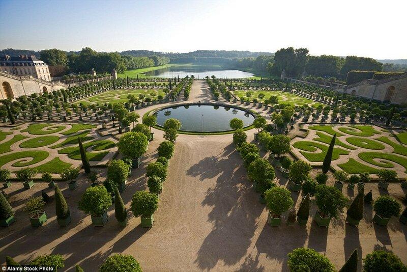 Дворцово-парковый ансамбль Версаль в пригороде Парижа, Франция. На фото: оранжерея Версаля и кадки с растениями в Версальском парке.